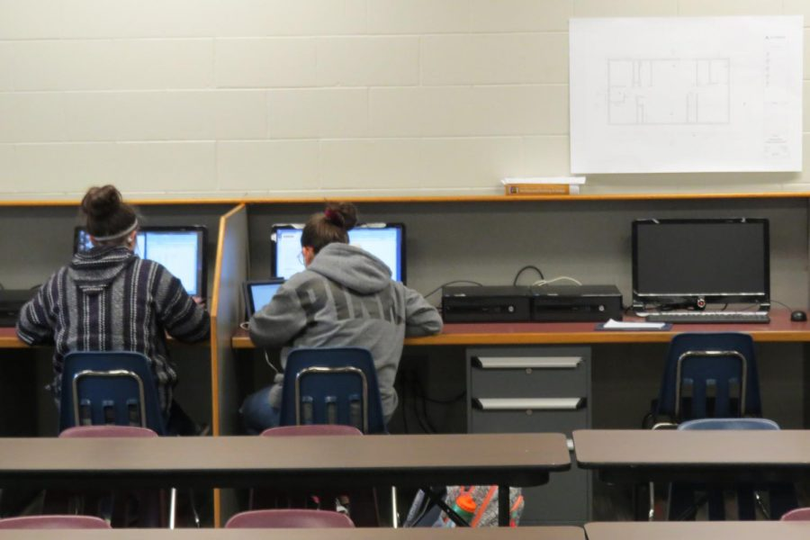 Two students work carefully in Mr. Linn's DMT class.