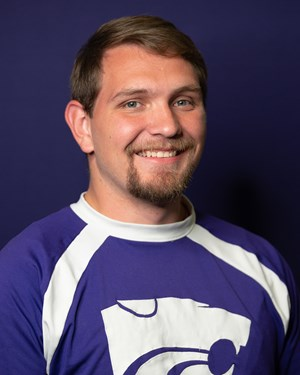 Zach Cooper, AHS agriculture teacher and FFA Adviser, is also a cheerleader for Kansas State University.  Photo credit: kstatesports.com