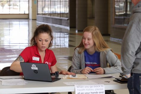 Senior Beth Holmes works with a Red Cross worker at a blood drive earlier this year.