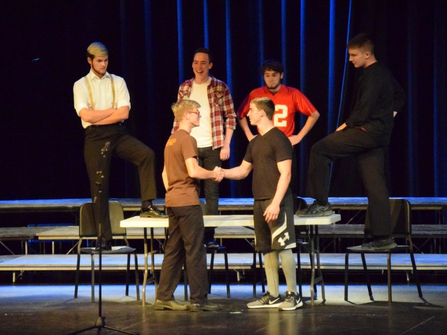 Braydon (front left) shakes hands with Dakotah Whiteley during a skit based on a song featured in The Greatest Showman during the Fall 2018 vocal music concert.